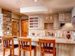 Lower level kitchen with breakfast bar, granite counters, white oak cabinets showcasing a custom wine cabinet.