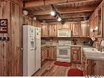 Full kitchen with microwave, electric stove full fridge with all dishes, silverware and kitchen gear