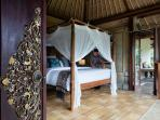 The spacious main bedroom upstairs with a king-size, extra-length Balinese teak bed.