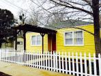Bright and cheery yellow exterior with white picket fence
