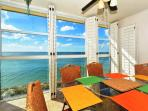 Dining area on lanai with floor-to-ceiling windows overlooking Gulf and beach below
