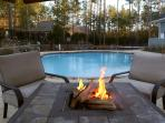 Patio with fire pit by pool area