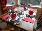 Dining table set for four. The table extends to seat 6 people.