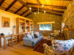 Stylish, cosy open plan sitting room with natural wood high ceiling. wooden furniture is handcrafted