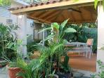 Gazebo in a tropical garden with comfortable seating.