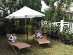 Private tropical garden with loungers & umbrella