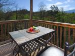 Pub table with 2 bar stools on Middle Level Deck with a view of Cove Mountain.