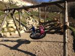 Adventure playground with slide, large birds nest swing, log climbing frame and trampoline.