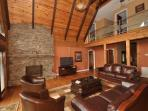 The large main floor living area has quality leather furniture, stone fireplace, & large flat screen