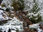 Landscaped waterfall during a winter snowfall.