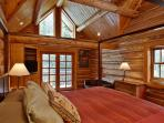 Master bedroom with a king sized bed sitting area and deck