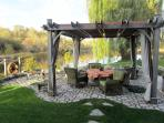 Dining and relaxing on the patio by the river.  Weber barbeque/induction hot plate for outdoor meals