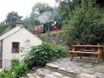 There is a steeply terraced garden and patio area to the side of the cottage, with picnic bench, and views of the steam...