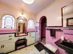 Spacious master bathroom with original purple and black tile from 1929