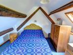 The traditionally furnished double bedroom has beamed, sloping ceilings with some limited headroom