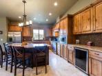 The kitchen features a custom kitchen island, which further extends the entertainment space and has a breakfast bar...