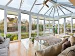 The large and airy conservatory is flooded with natural daylight and views of the river Thames