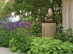 Blütenpracht im Juni in Kombination mit Shona-Skulpturen aus Zimbabwe.