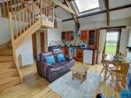 The open plan living area has a staircase leading up to the single bedroom