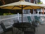 Umbrellas and tables and lounge chairs in our pool area.