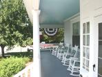Comfortable rockers on front porch with flag bunting for the Fourth of July