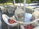 Two lovely sets of wicker dining furniture along side porch for dining al fresco
