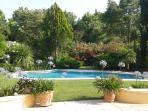 La piscine et le jardin paysagé vus depuis le salon de jardin sur la grande terrasse ombragée