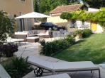 La terrasse et salon de jardin et le stationnement de véhicules vus depuis la terrasse de la piscine