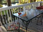 back deck with small dining table and grill overlooking the lagoon.