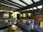 Oak panelled living room beneath the beams
