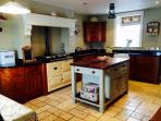 Traditional farmhouse kitchen with modern appliances.  The Aga cooker warms the heart of the home