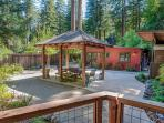 Outdoor dining area from the cottage porch w/main house & redwoods in background