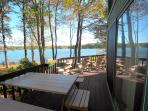 picnic table on deck overlooking yard and lake
