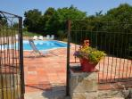 Swimming pool with shallow end and stairs protected bu a childproof gate. with lounger and chairs