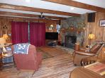 Living room with wood burning fireplace and sliding door to deck and hot tub