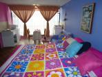 Primer plano cama King size de 3 plazas, ventana grande, apartamentos Arco Iris sus colores.