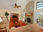 Living room provides plenty of space to relax by the stone fireplace.