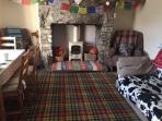 Sitting room - woodburning stove, dining table, sofa, books and games.