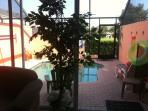 View of the Private Heated pool with large garden behind house.  Private pergola with swing and socc