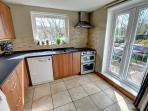 The fitted kitchen has a small freezer, dishwasher, washing machine and doors to garden