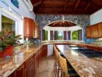 Gourmet Kitchen With an Island Cooktop. Native Blue Bits Stonework.