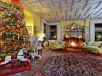 Living room with a grand piano, blazing fire & Christmas tree that's featured in Yankee Magazine!