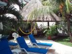 The palapa (palm leaf) roofed patio and a few of the lounge charis that are near the pool