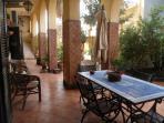 Ampio cortile porticato, con tavolo e sedie in ferro battuto, ombrellone e arredo da giardino
