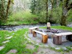 Fire pit with log benches and chairs along Big Creek.