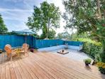 The decking and patio areas are enclosed by bright painted fencing