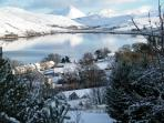 Glorious white and crisp winter.  Warehouses at Talisker nestled by Loch Harport,
