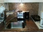 electric stove top with 2 burners, coffee maker, toaster, steamer, fridge and microwave.