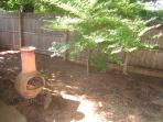 Portion of  back yard, gets dappled sun shade all day long in the heat of the summer. Charcoal grill