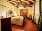 Elegant and charming grand bedroom. Decorated with antic furniture and spotlight affrescos.